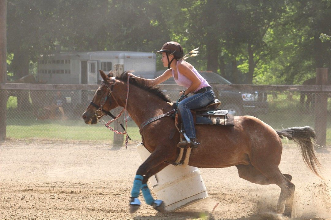 Bryndle Burks (11) pushes her horse to run home after turning the third barrel.
