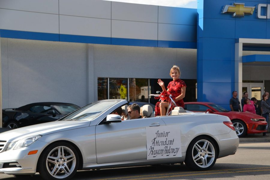 Waving at the camera, junior attendant, Reagan Ridgway, enjoys her time in the homecoming parade.