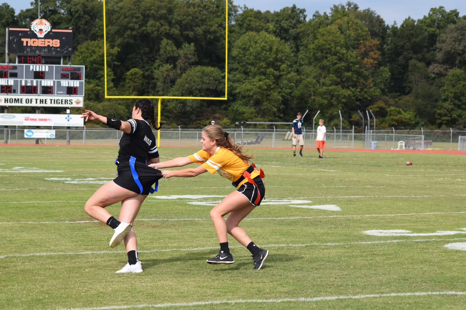 Cheyenne Hess (12) runs the ball while avoiding the grasps of Ashley Owens (11) during the powder puff game.