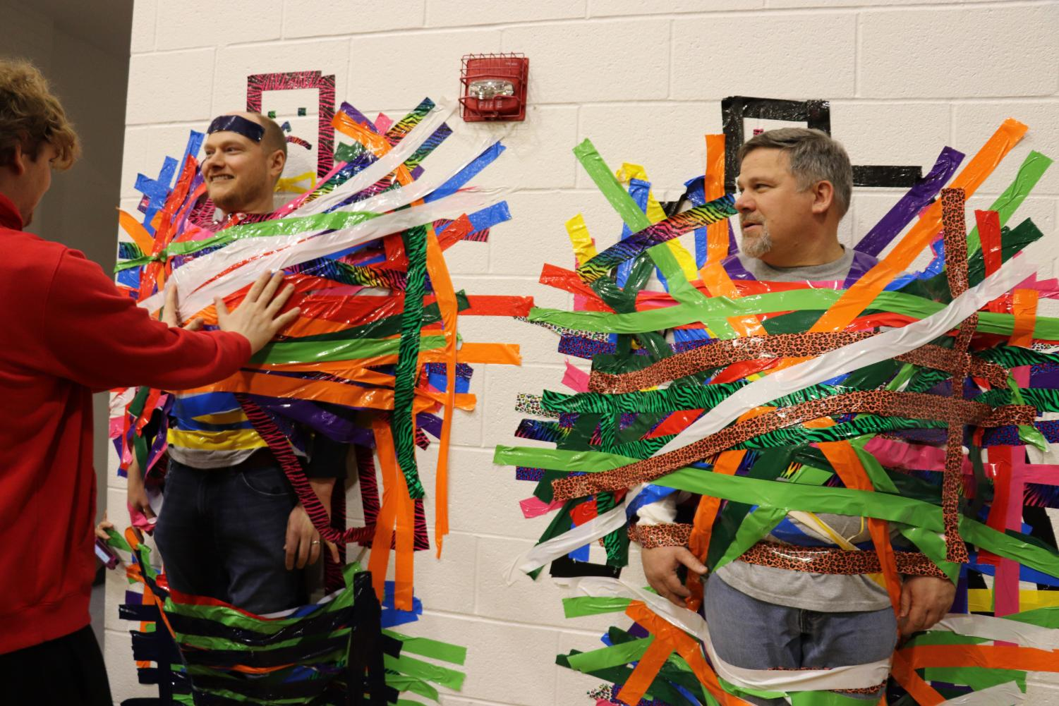 Assistant Principal Mr. Mason and Principal Mr. Johnson are duct taped to the wall for a fundraiser for Saint Jude's Children's Research Hospital.