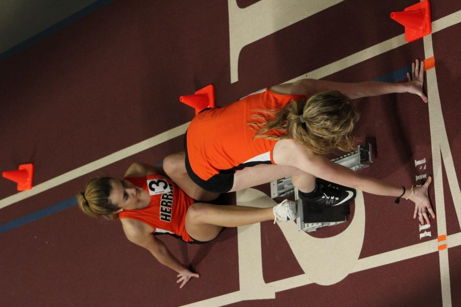 Breanna Gusewelle (9) helps Madison Blankenship (11) get ready to run the 200 meter dash at the SIU indoor invitational.