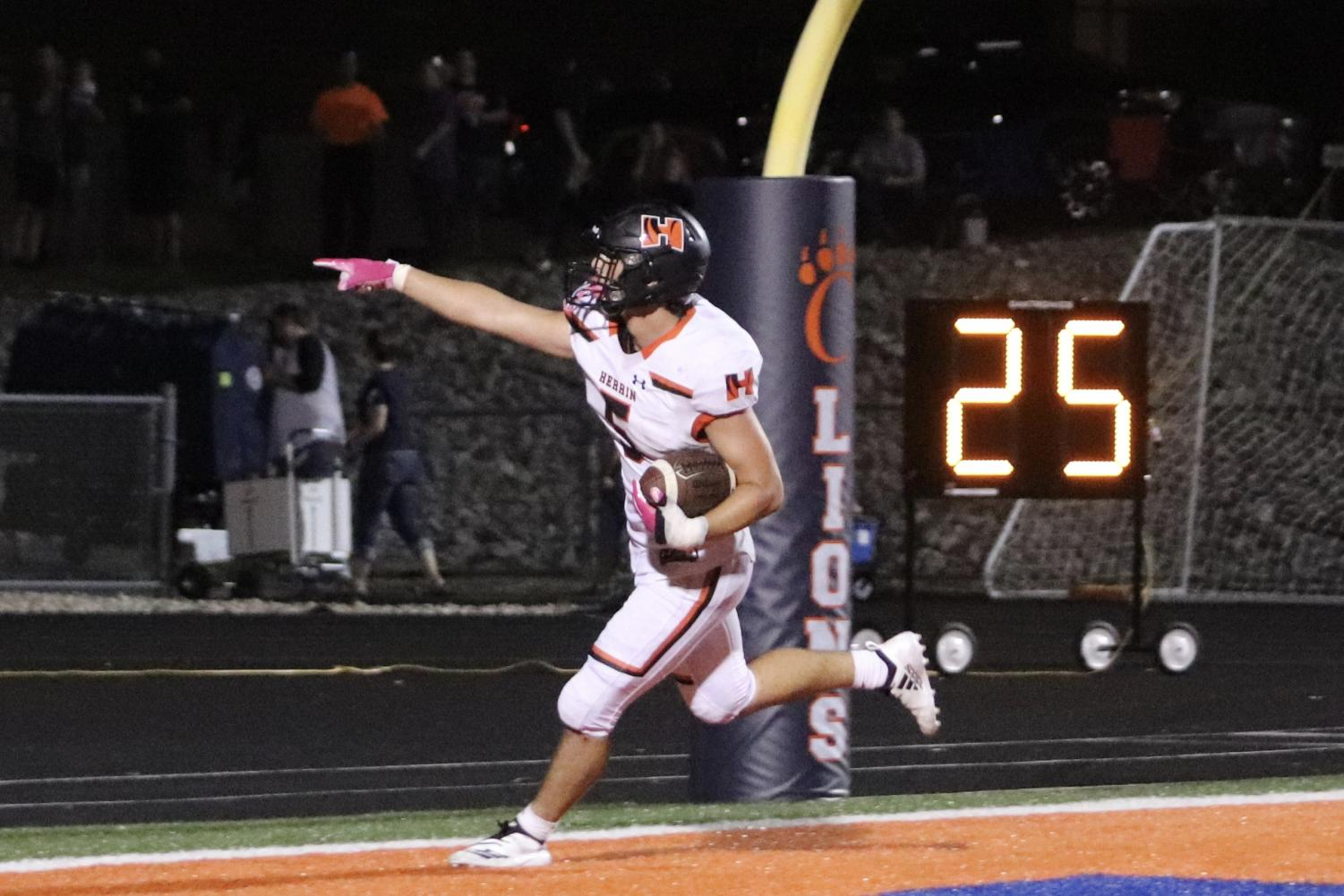 Cameron Damico (12) points to the student section after a phenomenal touchdown against Carterville.