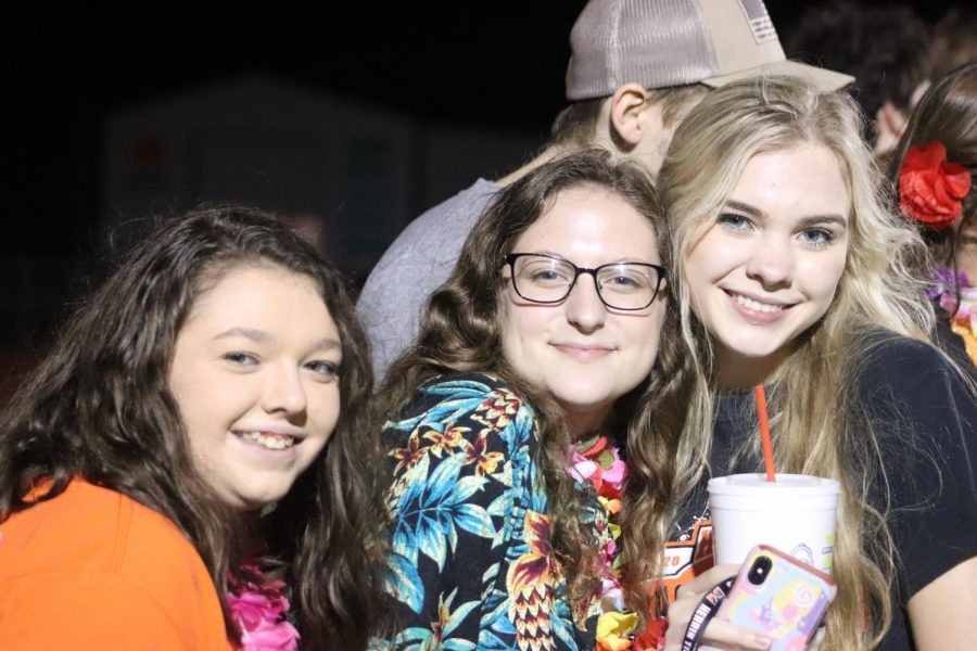 Mackenzie Hicks (11), Abigail Snider (11), and Kelsey Herkert (12) stand with the student section during the game.