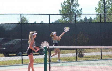 Breanna Nesler (11) watches as her doubles partner, Kelby Weber (11) follows through for a backhand at Sectionals on October 18 at Herrin.