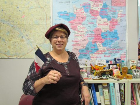 Mrs. Stanley poses with her mini French flag in front of her maps.