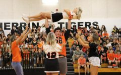 Logan Cole (12) proves his strength by lifting cheerleader, Lexi Price (12) above his head.