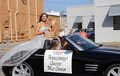 Homecoming queen Mia Connor (12), joyfully waves at the crowd.