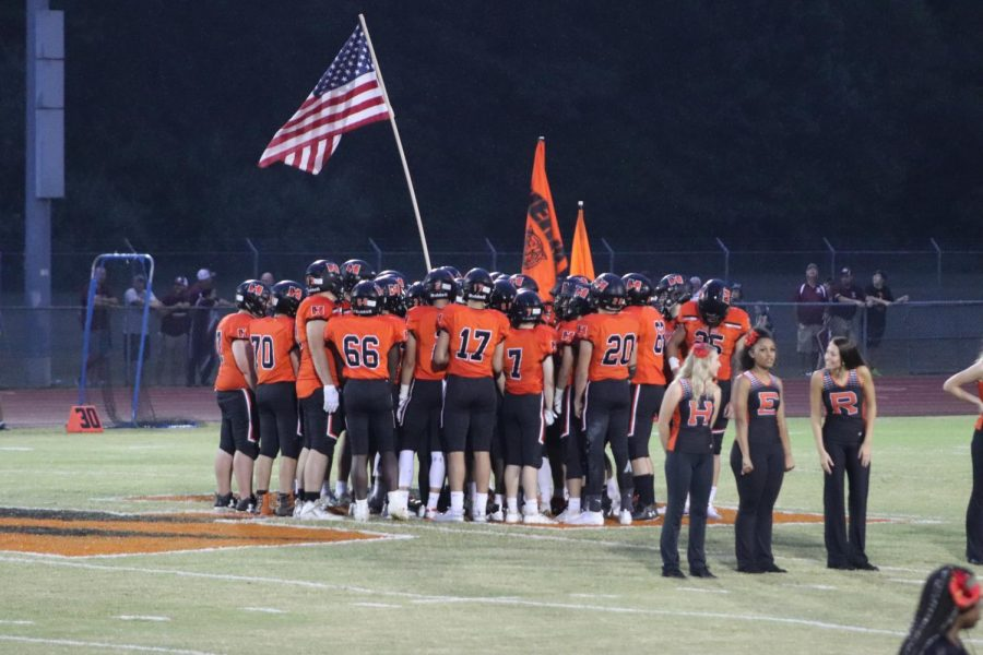 The football team huddles after running out for their game against Benton.