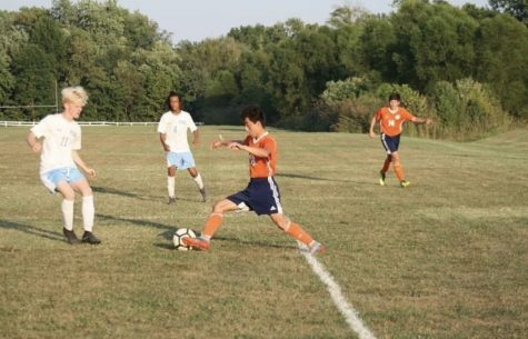 Jesus Mendez (10) runs toward the ball, passing a defending player.