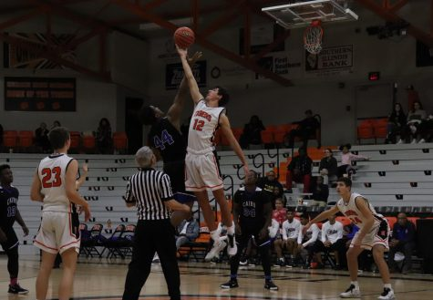 Luke LeQuatte (12) scores for the Tigers in the tip off of the game.
