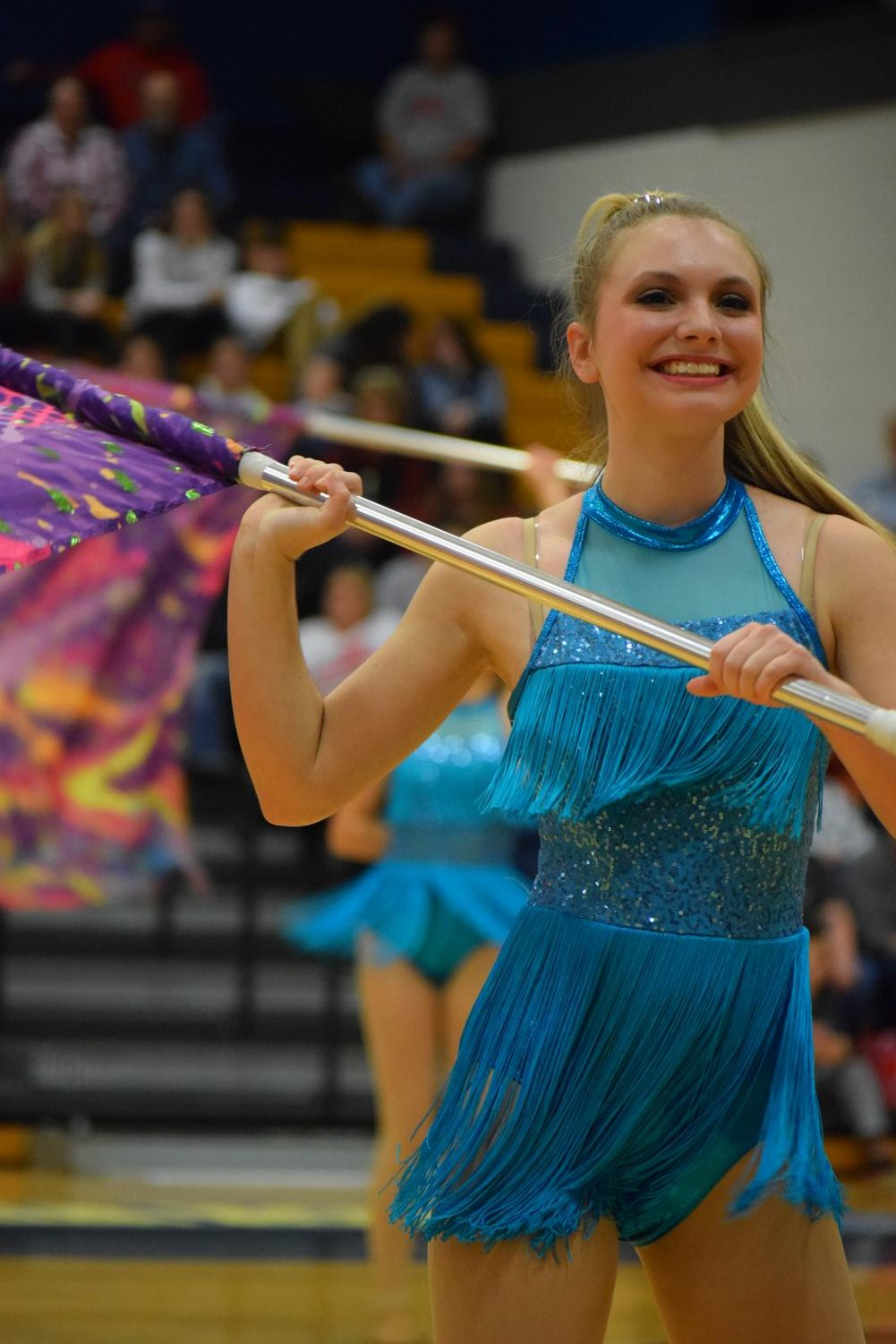 Kylie Watkins (11) smiles at the crowd after catching a partner toss at the Marion Regional Contest.