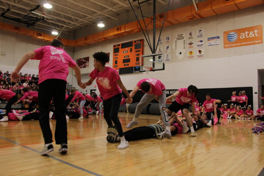 The boys basketball team competes in a game of Skin the Snake during the PINKOUT pep rally.