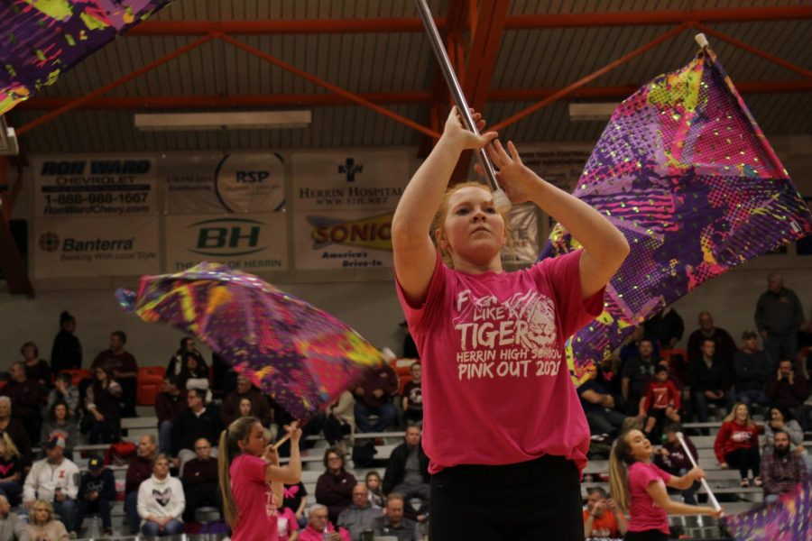 Rebecca Wilson (11) prepares for a toss during the flag teams half time performance.