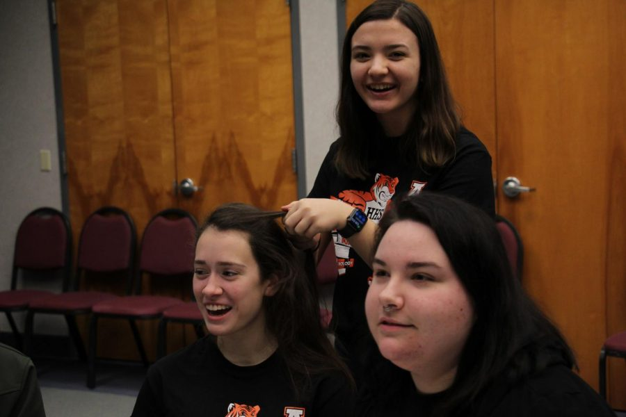 KELSEY- Maria Camarato (12) braids Ashton Hawk's (12) hair as Gabby Jones (12) looks on before the competition.
