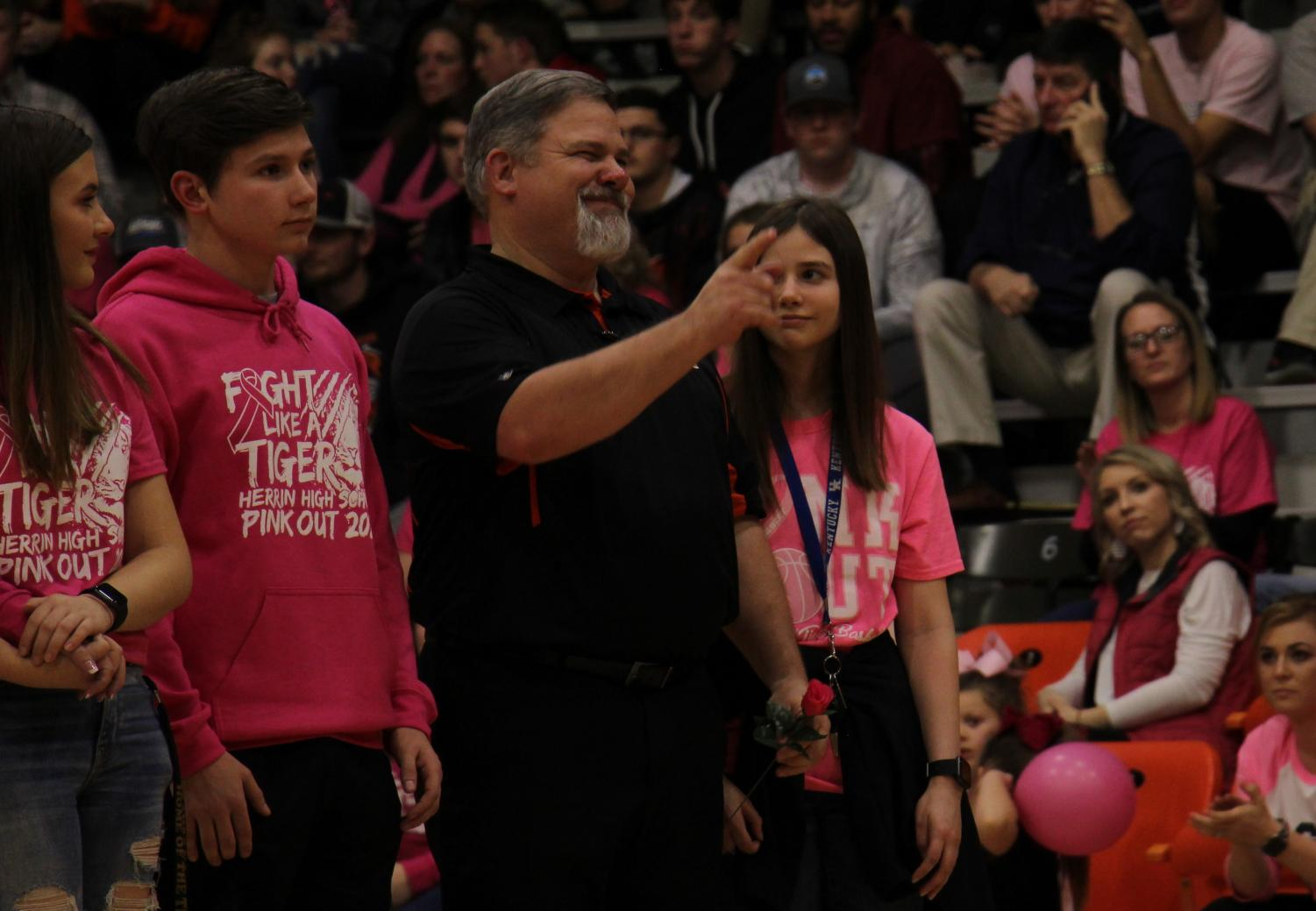 Mr. Johnson points out one of his supporters during the Rose Walk at halftime of the Pink Out game.