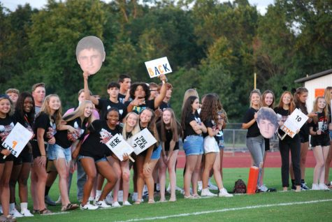 The student section smiles as they cheer on their football team.